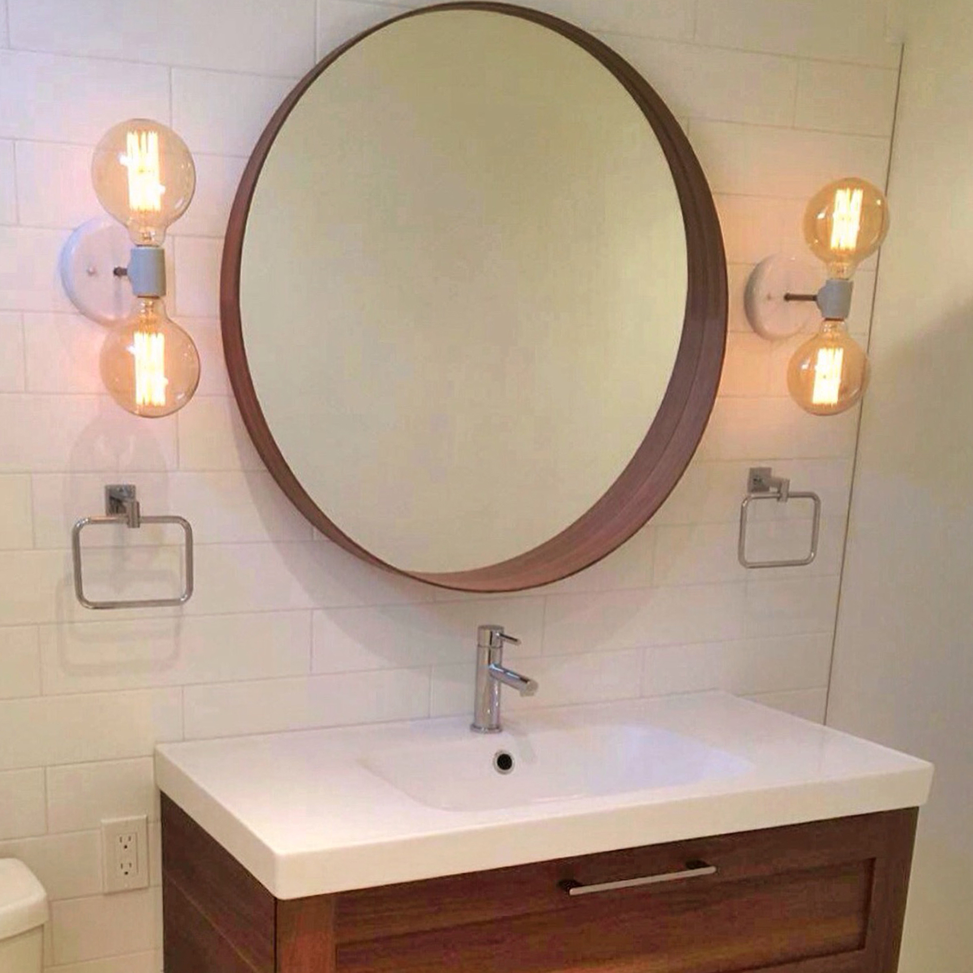 a pair of modern double light wall sconces above the bathroom sink