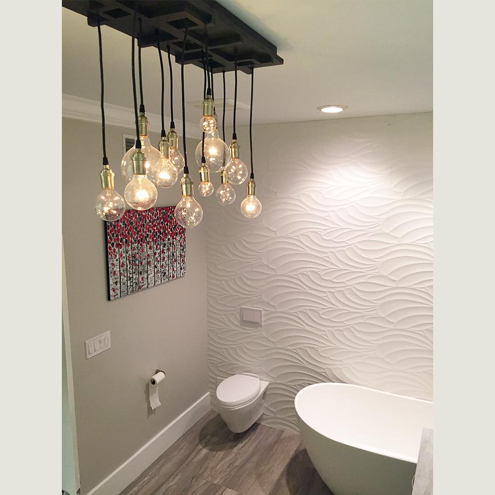 edison bulb chandelier by industrial lightworks hanging in a bathroom