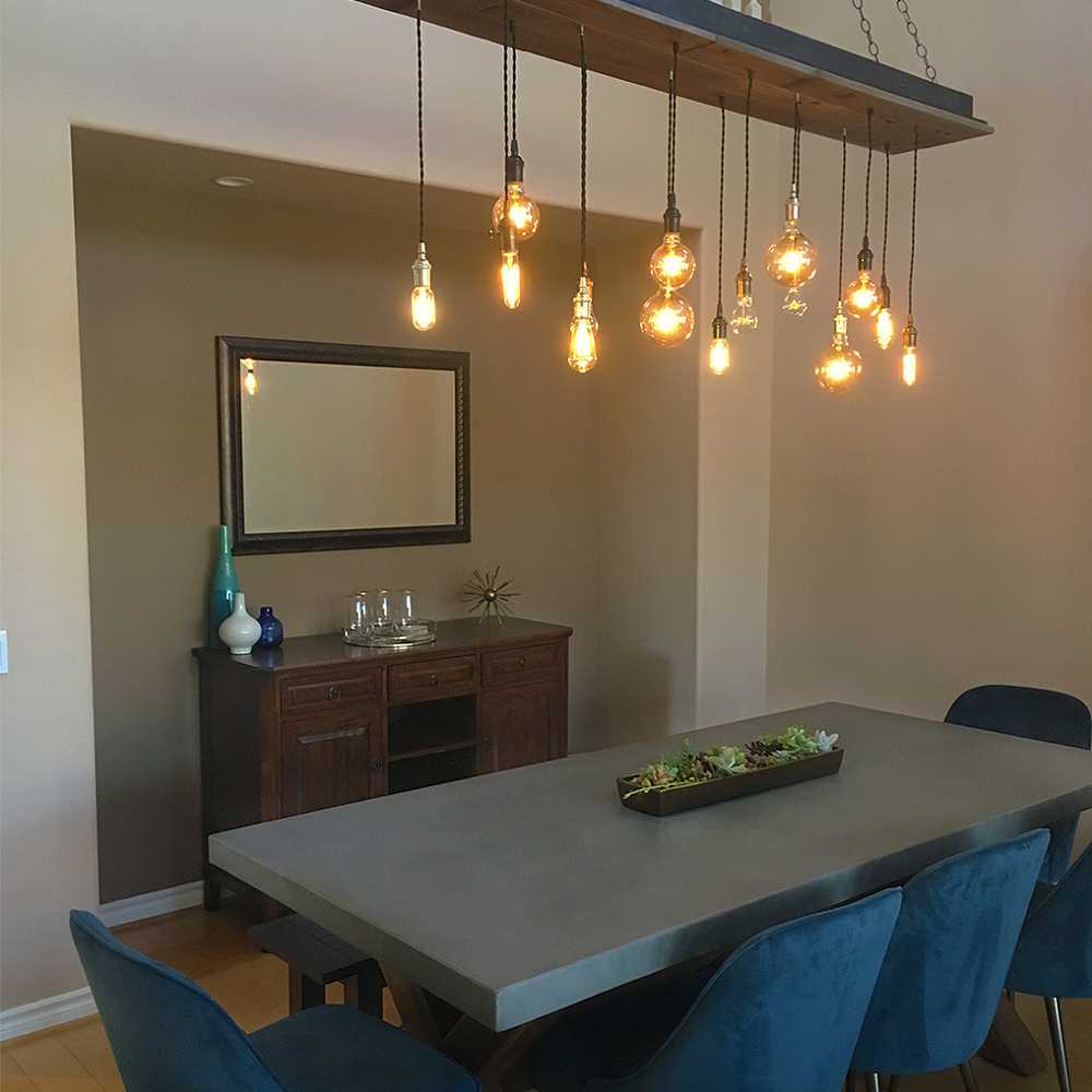 reclaimed wood chandelier hanging over a dining room table