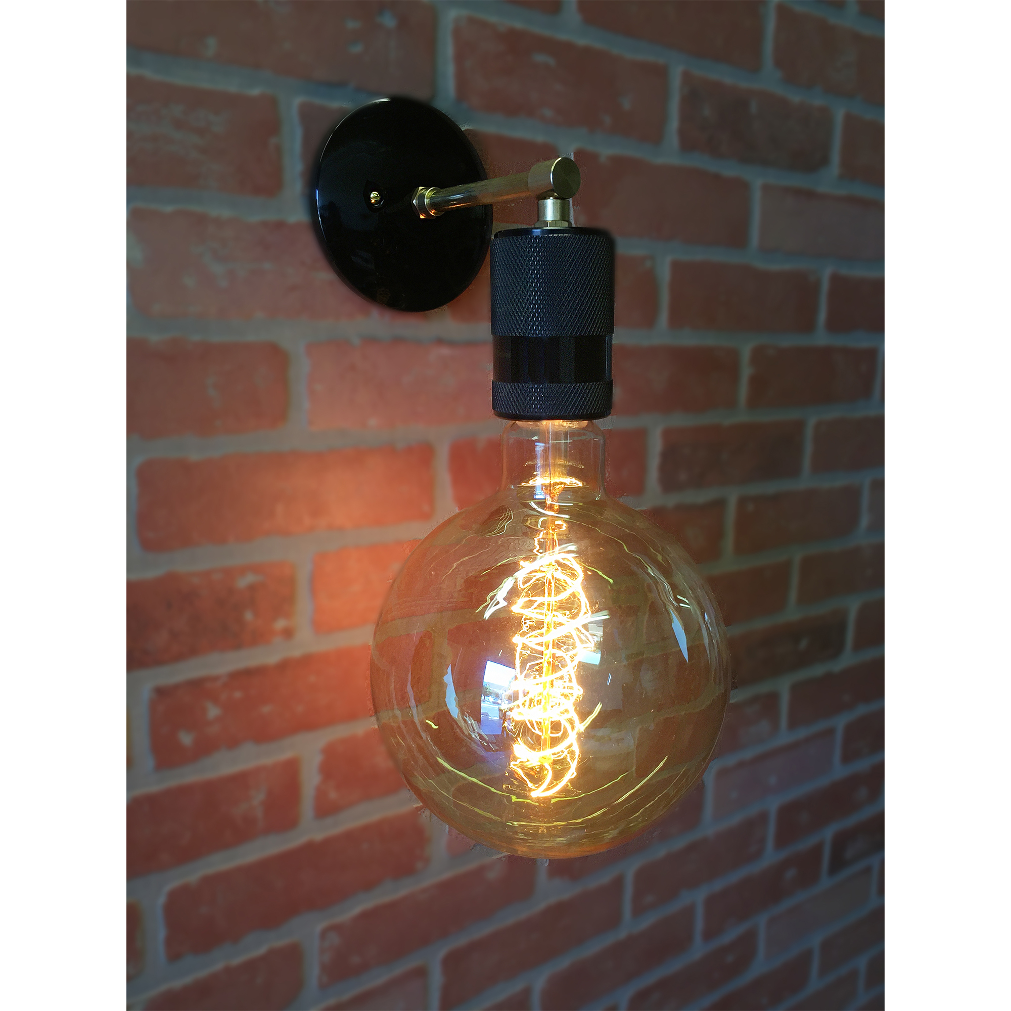 black metal and brass wall sconce with a extra large edison globe bulb